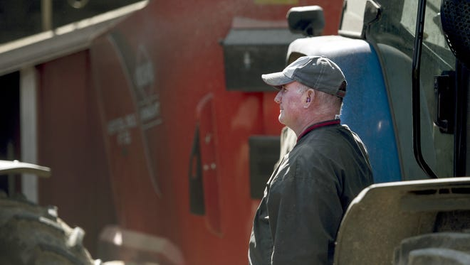 In a Tuesday, Oct. 17, 2017 photo, Jeff McNally, right, watches as a fellow Milton, Wis. farmer dumps high moisture corn into a gravity box in Milton, Wis. Farmers from the community helped Jeff with farm work after the recent death of his father, Tom McNally.