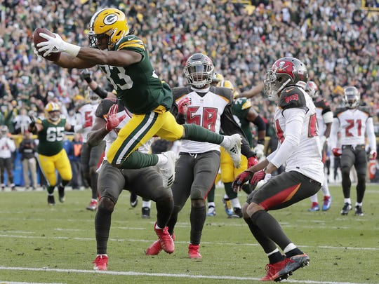 Green Bay Packers running back Aaron Jones (33) dives into the end zone to score the game-winning touchdown in overtime against the Tampa Bay Buccaneers on Dec. 3, 2017, at Lambeau Field.