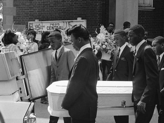 Pallbearers carry the tiny casket of Tonia Blanding,