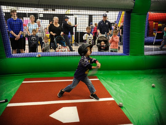 Five-year-old Hank Truelove takes a swing at a pitch