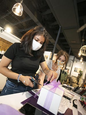 Fabiola Mendez, left and Vanessa Minyard, right, wrap gifts for a customer in the gift store Agapanthus in downtown Ocala on Monday afternoon. An Ocala attorney recently filed a lawsuit seeking an injunction to stop enforcement of an Ocala face mask ordinance.