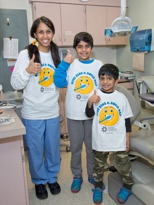 Dr. Varsha Agnihotrilends a smile with Rayyan and Agil Gudur of Edison during the Give Kids a Smile Day at JFK Medical Center.