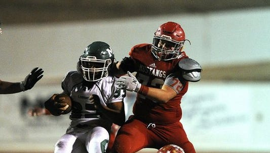 Monahans running back Tylan McCalister (33) is tackled for a loss by Sweetwater defensive lineman Tate Rainey (72) and defensive back Alex Gallegos (25) during the fourth quarter of Sweetwater's 19-16 loss on Friday, Oct. 28, 2016, at the Mustang Bowl in Sweetwater.