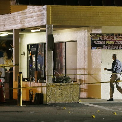 Police work the scene of a fatal shooting Monday, July