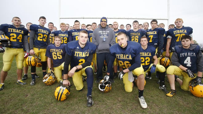 "Ithaca head coach Terry Hessbrook, shown here surrounded by the 2013 Yellowjackets, is the star of the documentary, ""Ithaca: The Climb."""