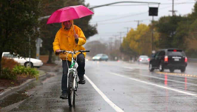 Bidur Pokharel shields himself from the rain as he bikes in Santa Rosa, Calif., on Feb. 26.