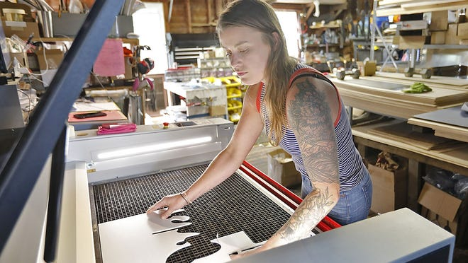 Natalie loads a sheet of plastic in the CNC laser cutter.  Natalie Chochrek of Plymouth is the owner of 1620 Designs who creates laser cut signs and logos on Monday September 14, 2020  Greg Derr/ The Patriot Ledger