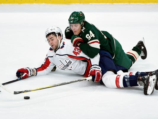 Washington Capitals' Tom Wilson (43) and Minnesota Wild's Mikael Granlund (64), of Finland, fall while going after the puck during the second period of an NHL hockey game Thursday, Feb. 15, 2018, in St. Paul, Minn. (AP Photo/Hannah Foslien)