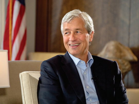 Jamie Dimon smiling while sitting on a beige chair.