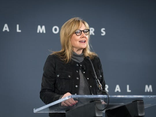 GM boss Mary Barra stood on a podium in front of a dark blue background from General Motors.