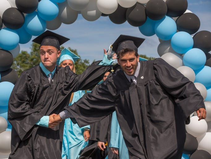 Two friends shake hands as they separate after walking under the arch at the 2014 Toms River East High School Graduation on June 25, 2014 in Toms River, NJ.   Photo by Peter Ackerman