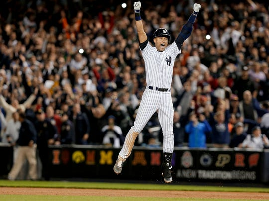 In this Sept. 25, 2014 photo, Yankees star Derek Jeter jumps after hitting the game-winning single against the Baltimore Orioles in the ninth inning of a baseball game, in New York. It was Jeter's last home game of his career at Yankee Stadium. Jeter's No. 2 is being retired, the last of the New York Yankees' single digits, on May 14 before a Mother's Day game against Houston, and a plaque in his honor will be unveiled in Monument Park during the ceremony.