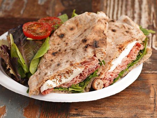 A slow-roasted ham with arugula and fresh mozzarella