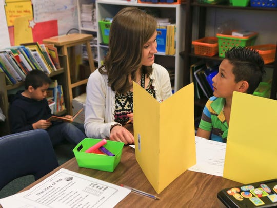 Teacher Rachel Manias works with student Jose Mauricio, 7, during a reading session at Parkwood Elementary School in Clarksville recently. The Clarksville elementary school has more than 50 percent of its students that are hispanic.
