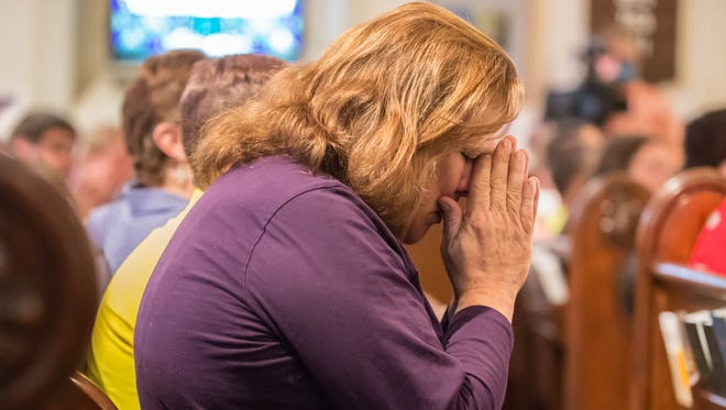 Tomi Ailene Morris  bows her head during the St. Thomas Episcopal Church vigil honoring the victims of the Sunday mass shootings at an Orlando gay nightclub.