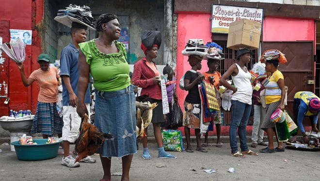 Street vendors in Port-au-Prince come to town with chickens in their hands and clothes and other merchandise balanced on their heads.