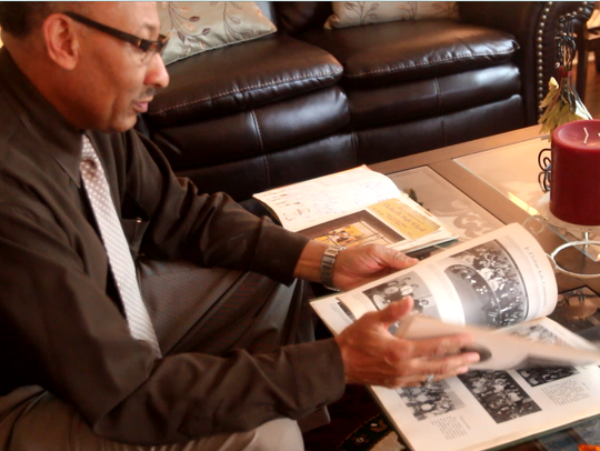 Clifford Adams flips through his class of '69 yearbook