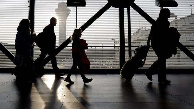 Travelers walk through terminal 3 at O'Hare International airport in Chicago. On top of the bag fees and other charges, families traveling this summer may have to pay extra just to sit next to one another.