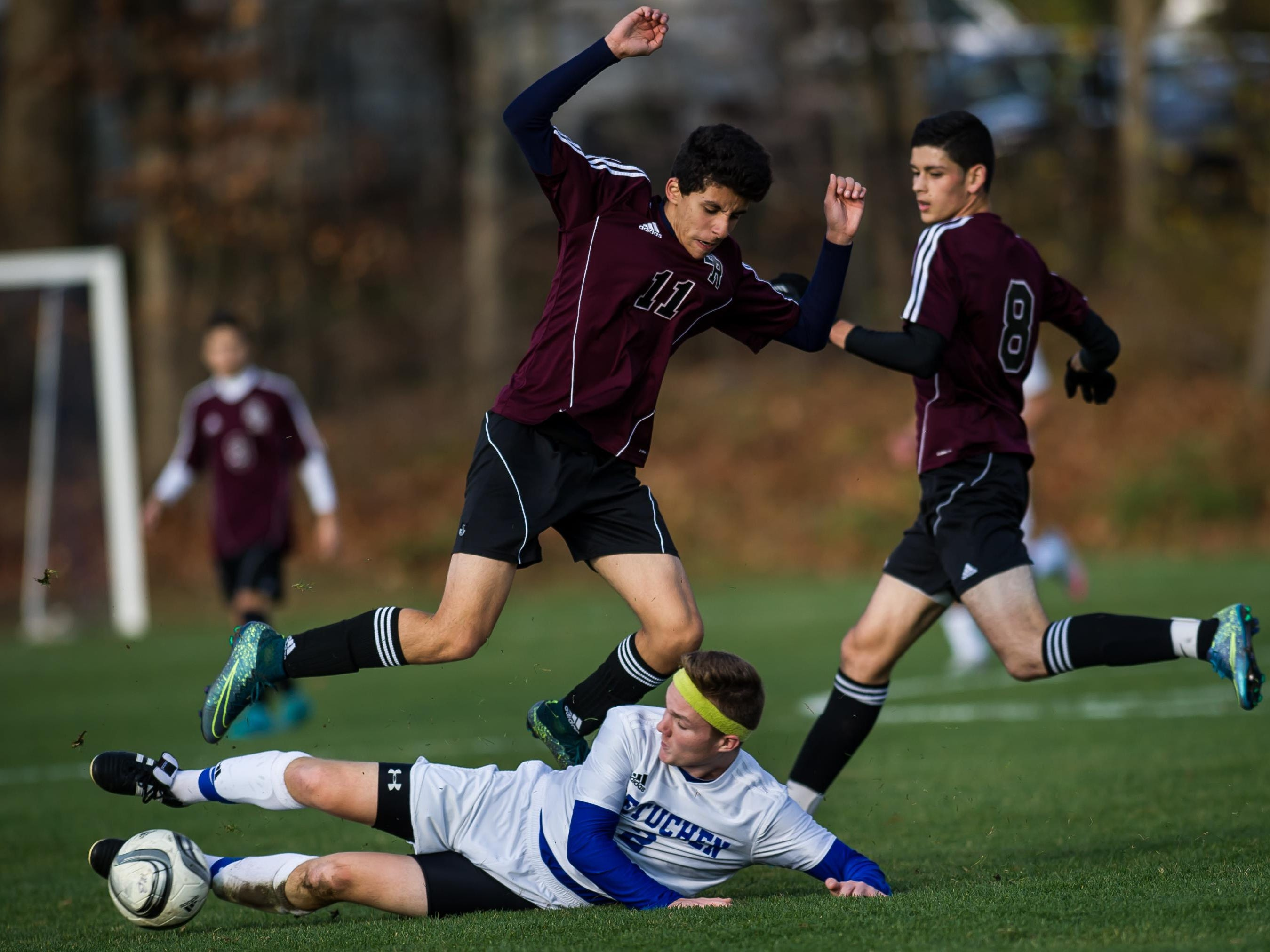 South River's Dennis Fernandes jumps over a sliding Mike Plunkett of Metuchen during their NJSIAA Central Group I sectional final on Friday at Metuchen High School.