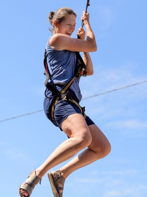 Emily Holt enjoys her ride on the Mobile Zip Line during the Lunch on the Lawn Bicentennial Birthday Bash at the Old Vanderburgh County Courthouse in Evansville, Ind., Friday, July 6, 2018. A company called Get Your Game On, Inc. set up the 28-foot-tall Spectrum Mobile Zipline on NW 4th Street between the Old Courthouse Center and the Old County Jail, pictured in the background.