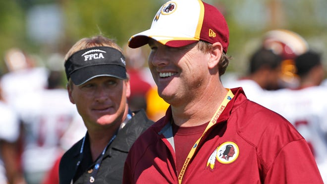 ESPN broadcaster and former NFL head coach Jon Gruden, left, walks with his brother, Washington Redskins head coach Jay Gruden, after a recent practice.
