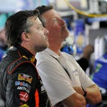 Tony Stewart, left, looks at a monitor during practice for Saturday's NASCAR Bank of America Sprint Cup series auto race at Charlotte Motor Speedway in Concord, N.C., Friday, Oct. 10, 2014. (AP Photo/Mike McCarn)