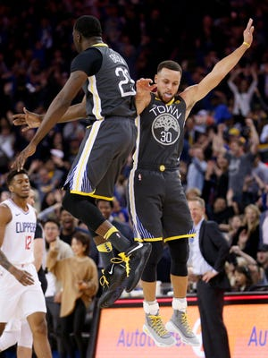 Stephen Curry celebrates with Draymond Green after making a three-point basket at the end of the first quarter against the Los Angeles Clippers at Oracle Arena.