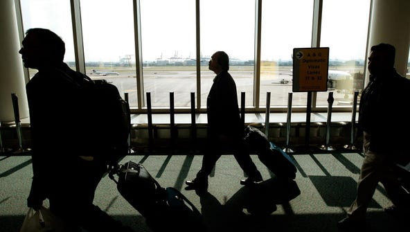 Travelers with bags walk toward the passport control