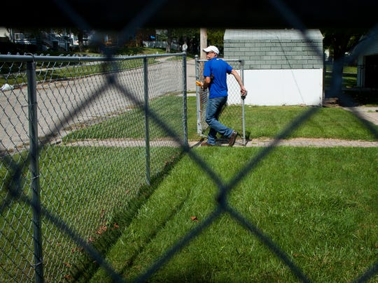 Water operator Wally Mencavage closes a gate after checking the water meter on a home Thursday in St. Clair.
