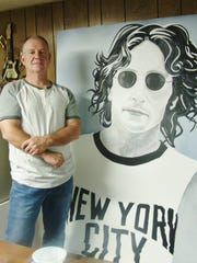 Frank Pettibone poses with his life-size painting of John Lennon.