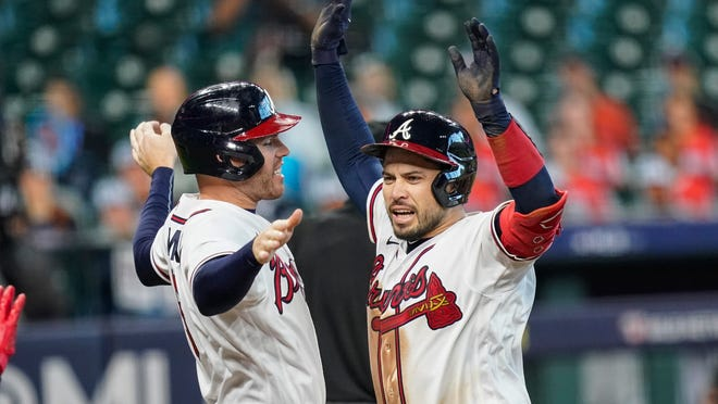 The Braves' Travis d'Arnaud, right, celebrates with teammate Freddie Freeman after hitting a three-run homet during the seventh inning in Game 1 of the National League Division Series against the Marlins.