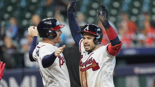The Atlanta Braves' Travis d'Arnaud, right, celebrates with teammate Freddie Freeman after hitting a three-run home run during the seventh inning in Game 1 of a National League Division Series against the Miami Marlins on Tuesday in Houston.