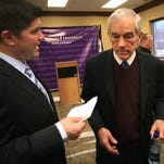 Then-presidential candidate Ron Paul, left, gets a schedule update from Jesse Benton, his National Press Secretary, after Paul spoke at Des Moines University.