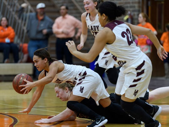 Henderson County's Jaylee Carter (5) takes possession in a fight for the ball against Webster County's Jessica Winders (31) in the Colonels' 64-53 win on Friday.