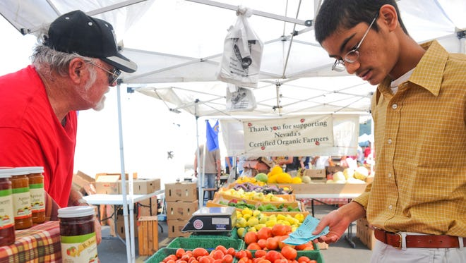 In this 2013 file photograph,  Karthik Rohatgi, right, talks to a vendor at the Reno Village Farmers Market.