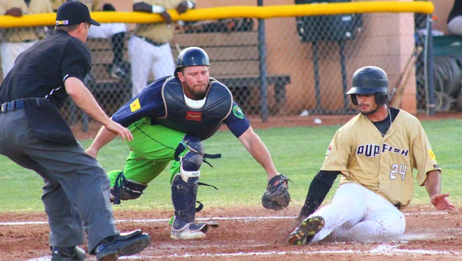 Dubal Baez, right, slides in ahead of the tag by Jim Smith on Monday evening at the Griggs Sports Complex.