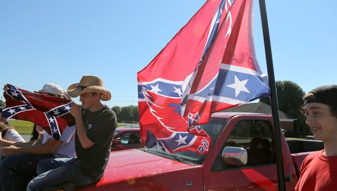 Christiansburg High School students display Confederate flags in a shopping center parking lot after being suspended from school in Christiansburg, Va., Thursday, Sept. 17, 2015.