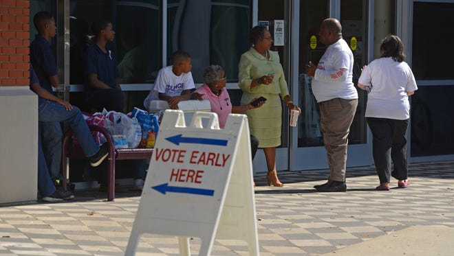 Volunteers offer free snacks and water to voters go in to vote Sunday at the West Florida Regional Library during Souls to the Polls, several African-Amercan community organizations and churches got the word out to go and vote. The collaborative groups even established free rides to the polls for voters in need of transportation.