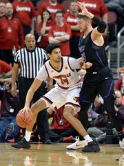 Louisville forward Anas Mahmoud (14) attempts to work