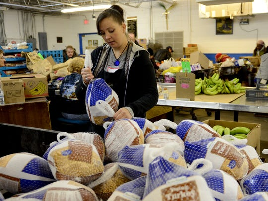 Volunteer Sierra Summers hands out turkeys as part of Thanksgiving dinner distribution at Paul's Pantry in Green Bay.
