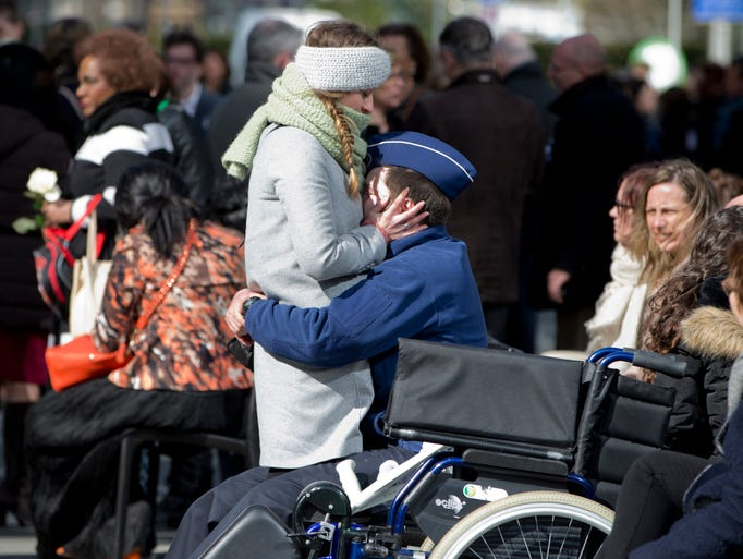 Two people embrace during a one-year anniversary service