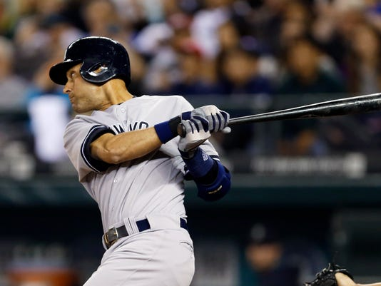 New York Yankees' Derek Jeter follows through on a two-run single in the fourth inning of a baseball game against the Seattle Mariners, Thursday, June 12, 2014 in Seattle. (AP Photo/Ted S. Warren)