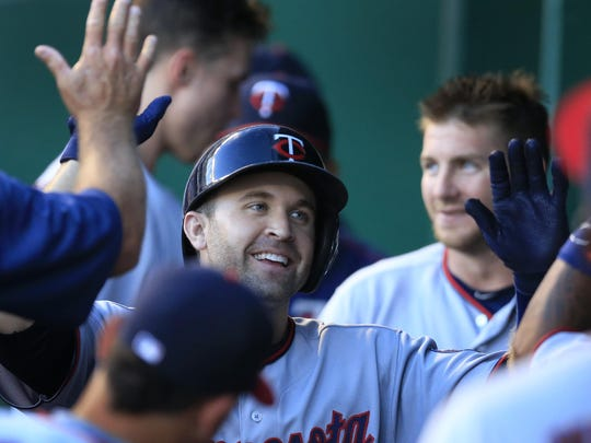 The Minnesota Twins' Brian Dozier is congratulated by teammates after his solo home run off Kansas City Royals starting pitcher Dillon Gee during the first inning Thursday at Kauffman Stadium in Kansas City, Mo.