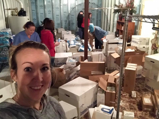 Jessica Edwards takes a quick picture while other members of their medical mission team get supplies ready for thier mission to the Dominican Republic.