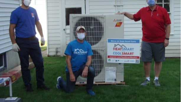One of the first Heat Pump installations through HeatSmart Newton, a city initiative, has been installed at the home of Tim Tippett. Pictured from left: Renato Mile, installer from New England Ductless; Craig Forman, coach for HeatSmart Newton; and homeowner Tim Tippett.