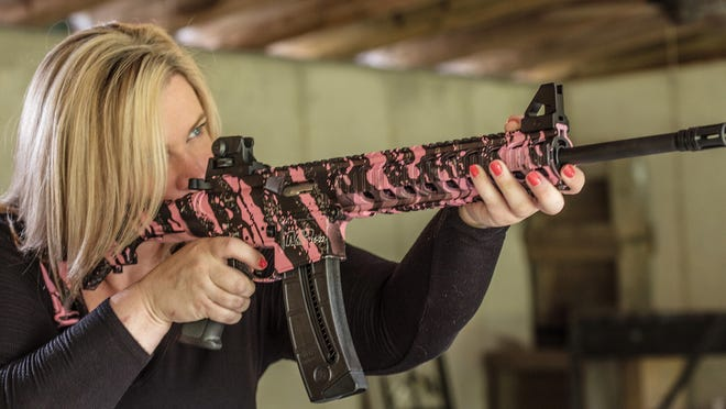 Dara Humphries, an NRA and Glock firearms instructor, poses for a portrait June 24, 2016, in Gainesville, Ga., holding an AR-platform rifle at a gun range.
