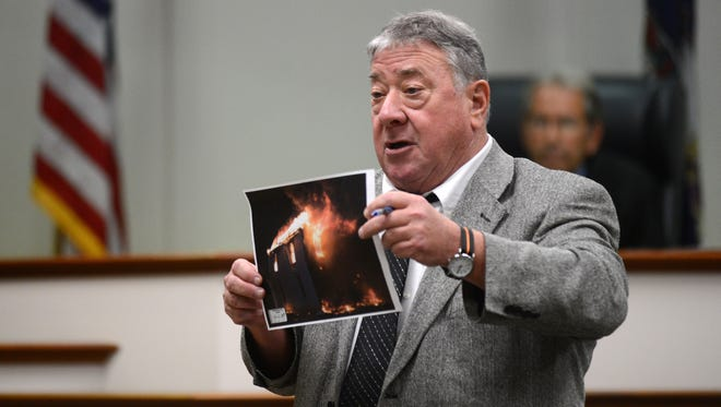 Commonwealth's Attorney Gary Agar shows the jury a photograph of the fire that destroyed a Keller house on March 3, 2013 during his closing arguments in the arson trial of Tonya Bundick in Vriginia Beach, Va. on Tuesday, July 15, 2014. Agar recently retired.