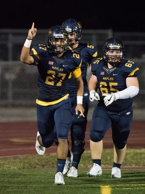Chez Mellusi of Naples celebrates with teammates after scoring a touchdown in the game against Sunrise-Piper at Naples High Friday night, November 3, 2017. The score put Naples up 42-0.