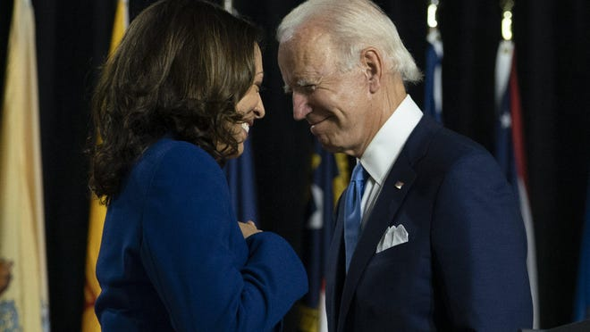 """FILE - In this Aug. 12, 2020, file photo, Democratic presidential candidate former Vice President Joe Biden and his running mate Sen. Kamala Harris, D-Calif., pass each other as Harris moves to the podium to speak during a campaign event at Alexis Dupont High School in Wilmington, Del. Harris made history Saturday, Nov. 7,  as the first Black woman elected as vice president of the United States, shattering barriers that have kept men â€"""" almost all of them white â€"""" entrenched at the highest levels of American politics for more than two centuries."""
