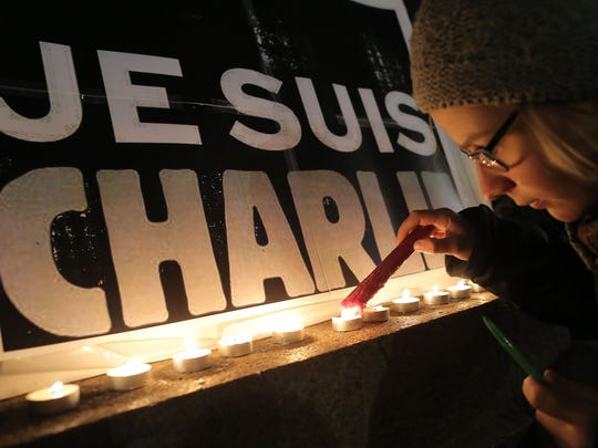 A child lights a candle next to a poster that reads,